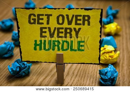 Writing note showing Get Over Every Hurdle. Business photo showcasing Overcome any obstacle problem trouble adversities Paperclip grip yellow page with text woody floor blue and yellow lob poster
