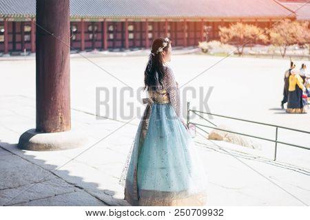 Young Asian Woman Traveler In Korean National Dress Or Hanbok Walking Traveling Into The Gyeongbokgu