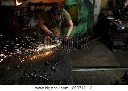 Blacksmith in workwear using electric handtool to process iron workpiece in smithy