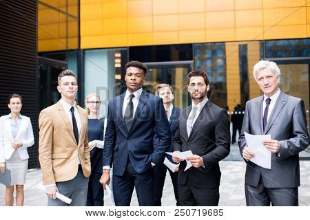 Group of confident intercultural businessmen in suits and their female colleagues standing not far from modern business center