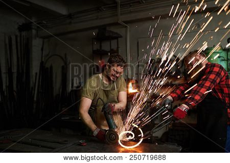 One of blacksmiths holding hot molten metal workpiece by pincers while his colleague processing it with electric handtool