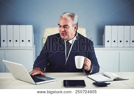 Happy Lively Male In Elegant Dark Suit Sitting At Office Desk With Cup Of Hot Drink And Working On L