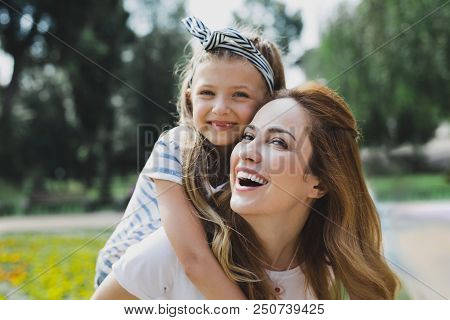 Beaming Daughter. Cute Beaming Daughter Hugging Her Loving Smiling Mother While Spending Time With H