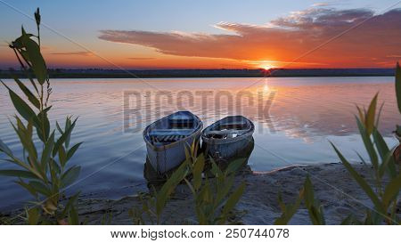 Two Old Wooden Boats Chained By The Shore Of A Calm River. Early Morning, The Rays Of The Rising Sun