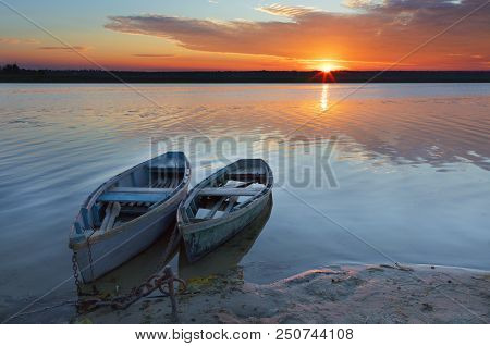 Two Old Blue-green Wooden Boats Chained By The Shore Of A Calm River. Early Morning, The Rays Of The