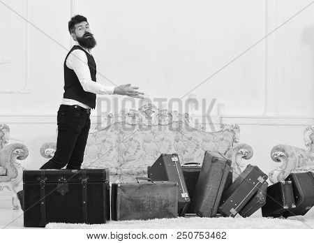 Macho Elegant On Careless Face Dropped Pile Of Vintage Suitcases. Man With Beard And Mustache Wearin