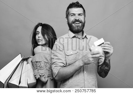 Guy With Beard And Lady With Smiling Faces Do Shopping. Man With Beard Holds Credit Card And Money B
