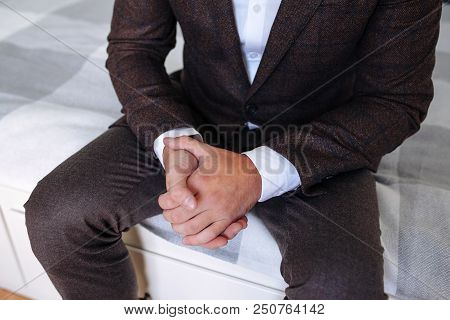 Man Sitting With His Hands Crossed. Men's Hand In A Brown Suit, Watch On The Man's Hand, The Hand Of