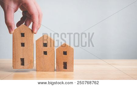 Property Investment Real Estate And House Mortgage Financial Concept. Hand Holding Wooden Home On Ta