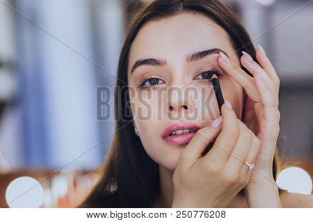 Black Eyeliner. Unbelievably Beautiful Young Dark-haired Woman Using Black Eyeliner While Putting Ma