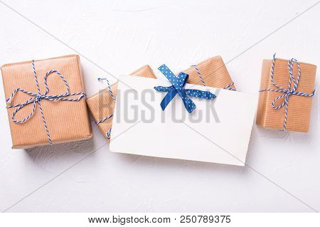 Empty  Postcard And Wrapped  Gift Boxes With Presents  On Textured Background. Selective Focus Is On