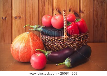 Fresh Vegetables In Basket On Wooden Table Against Wooden Wall