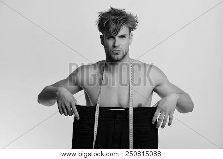 Fashion And Size Concept. Athlete With Messy Hair And Naked Torso. Man Holds Black Jeans Of Large Si