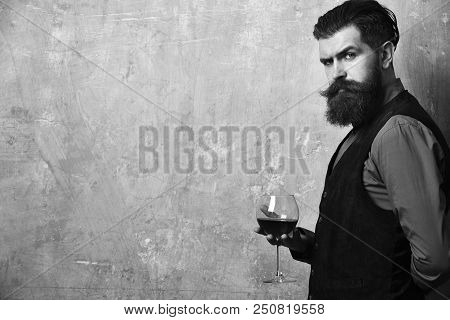 Degustator With Glass Of Red Wine. Sommelier With Confident Face Drinks Wine Glass. Man With Beard A