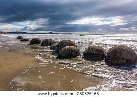 Boulders Moeraki - a group of large spherical boulders on the beach Koekokhe. Ocean tide. Travel to New Zealand. The concept of active, eco and photo tourism
