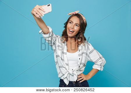 Portrait of brunette beautiful woman 20s wearing headband smiling and taking selfie on mobile phone isolated over blue background