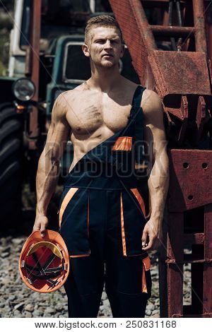 Metal Worker. Metal Worker Rest At Heavy Machinery. Handsome Metal Worker In Working Uniform. Strong