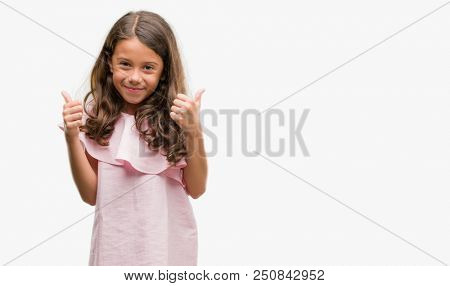 Brunette hispanic girl wearing pink dress success sign doing positive gesture with hand, thumbs up smiling and happy. Looking at the camera with cheerful expression, winner gesture.