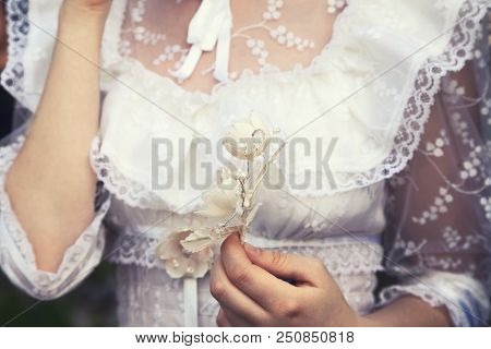 Young Virgin Girl In A White Lace Wedding Dress Holding A Flower. Tender Delicate Woman At A Wedding