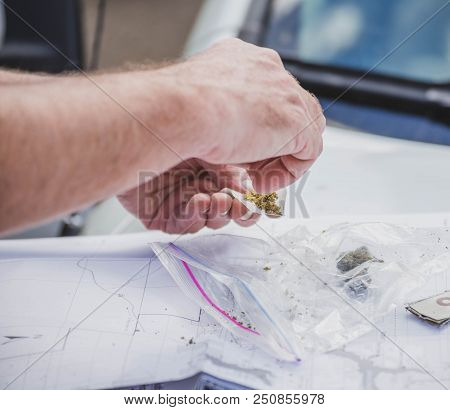Person Rolling A Cannabis Joint Outdoors