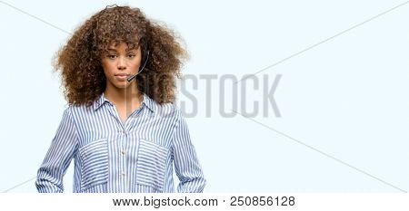 African american call center operator woman with a confident expression on smart face thinking serious