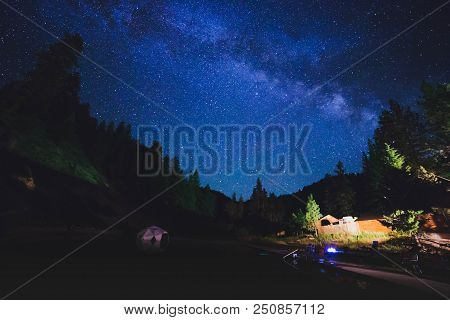 The Milky Way Shines In A Night Sky Above Buildings And A Natural Outdoor Pool.