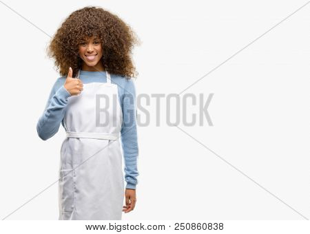 African american shop owner woman wearing an apron smiling broadly showing thumbs up gesture to camera, expression of like and approval