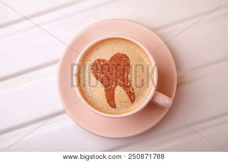 Cup Of Coffee With Tooth On Foam. Coffee Spoils Teeth And Makes Them Yellow. Morning Coffee Or Coffe