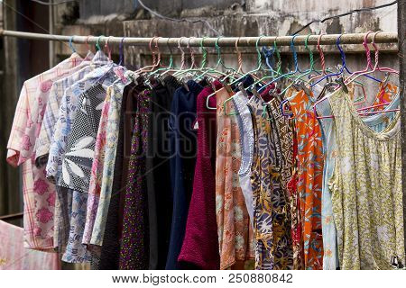 Clothes are hung outdoors primarily from where there is a wash. poster