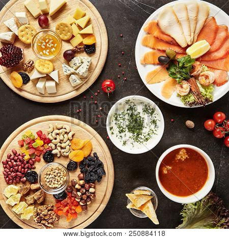 Wine Plates with Cheese Mix, Dried Fruits and Nuts on Wooden Plate and Fish Plate Top View. Cheeseboard with Pieces of Various Cheese such as Cheddar, Edam, Camembert