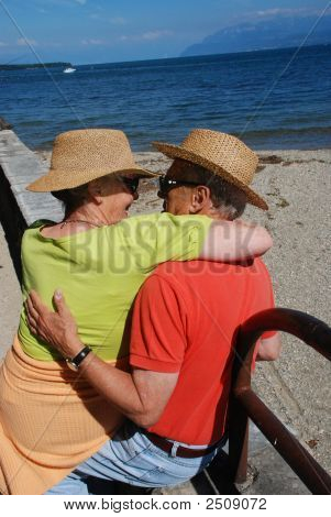 Romantic Elderly Couple Embracing By The Lakeside