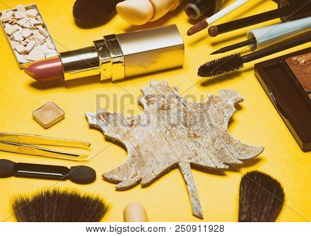 Autumn Makeup In Retro Style. Make-up Products Brown And Golden Colors With Maple Leaf Made Of Bark.