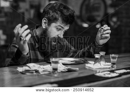 Guy holds rolled banknote, defocused background. Hipster with beard sniffs cocaine, drug. Man with shocked face looking at metal salver with drug. Get high and dope concept. poster