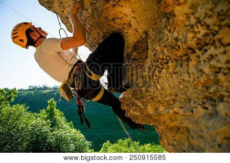 Image Of Tourist Man In Helmet Clambering Up On Cliff.