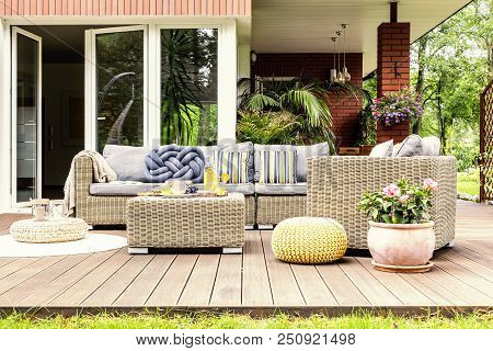 Garden Table With Fruits And Fresh Orange Juice Standing On Wooden Terrace With Plants, Armchair And