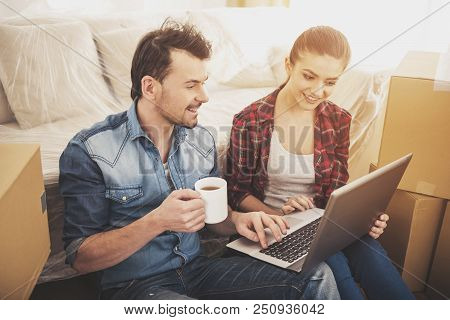 Happy Couple With Laptop. Choose Stuff In New Flat. Young Happy Europeans. Things For Apartments. Ma