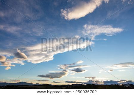Sunlight concept. Cloudy sky at sunrise, sunset over mountain range, copy space, wallpaper.