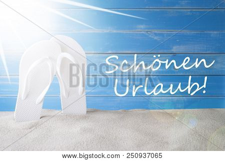 German Text Schoenen Urlaub Means Happy Holidays. Sunny Summer Greeting Card With Sand And Flip Flop