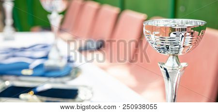 Champion awards concept. Silver trophy cup on a table with bokeh background.