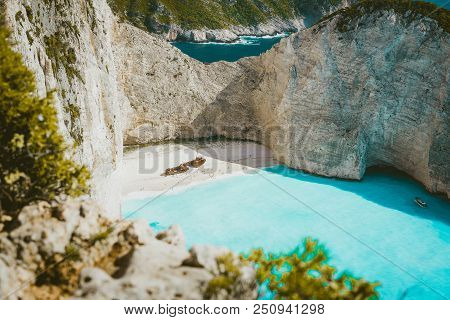 Famous Shipwreck On Navagio Beach With Turquoise Blue Sea Water Surrounded By Huge White Cliffs. Fam