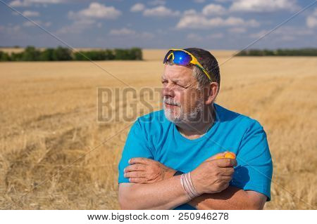 Outdoor Portrait Of A Bearded Senior In Sunglasses Taking Apricots In The Hand Against Blue Cloudy S