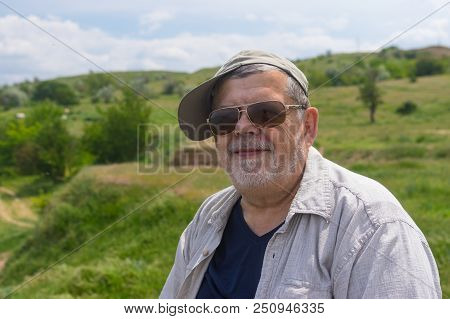 Outdoor Portrait Of Happy Ukrainian Countryman Against Hilly Spring Pasture
