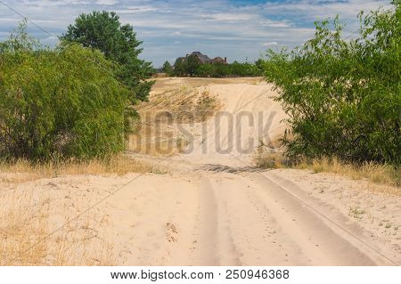 Landscape With Sandy Track Leading To Human Settlement