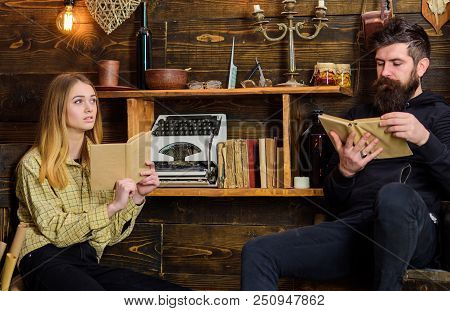 Soulful evening concept. Father instills love to books for his daughter. Family spend pleasant evening with books, interior background. Girl and man on calm faces reading book in warm atmosphere. poster