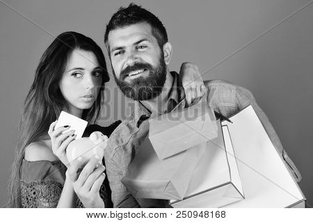 Shopping And Free Time Concept. Man With Beard Holds Credit Card And Piggy Bank. Couple Holds Shoppi