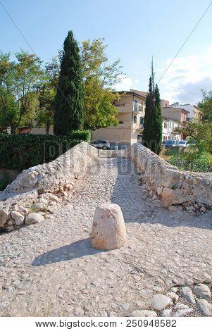 MAJORCA, SPAIN - SEPTEMBER 4, 2017: The Roman bridge across the Torrente de Sant Jordi at Pollenca on the Spanish island of Majorca. The actual origin of the bridge is unconfirmed.