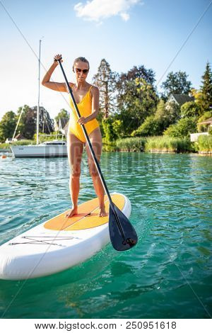 SUP Stand up paddle board concept - Pretty, young woman paddle boarding on a lovely lake in warm late afternoon light