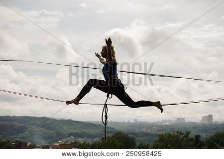 Young blondie woman trying to sit on twine on the slackline rope on the background of houses among trees and clear sky poster