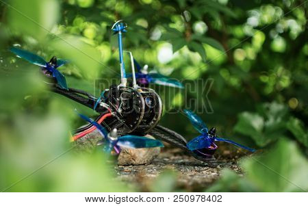 Blue race drone for fpv first person view for racing with quadcopters with vibrant colors in nature green background. poster
