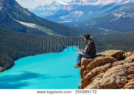 A Hiker Sitting On The Edge Of Bow Summit Looking At Peyto Lake In Banff National Park On The Icefie